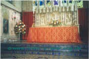 The high altar and sanctuary adorned for Pentecost.